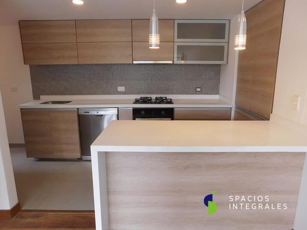 Cocina Integral con manijas tipo Gola, puerta marco aluminio y vidrio mini boreal, campana incrustada.