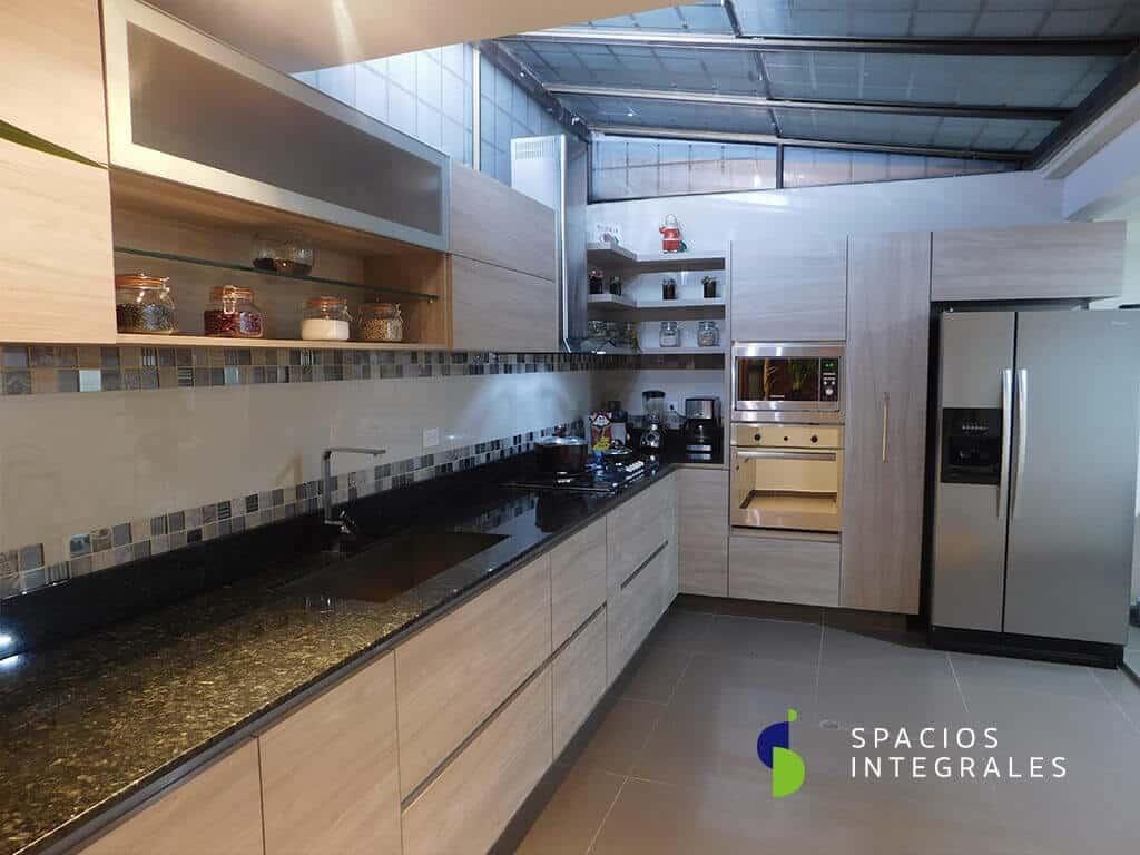 Cocina Integral con torre de hornos, alacena extraíble y mueble sobre nevera. Módulo pared decorativo abierto con entrepaño en vidrio