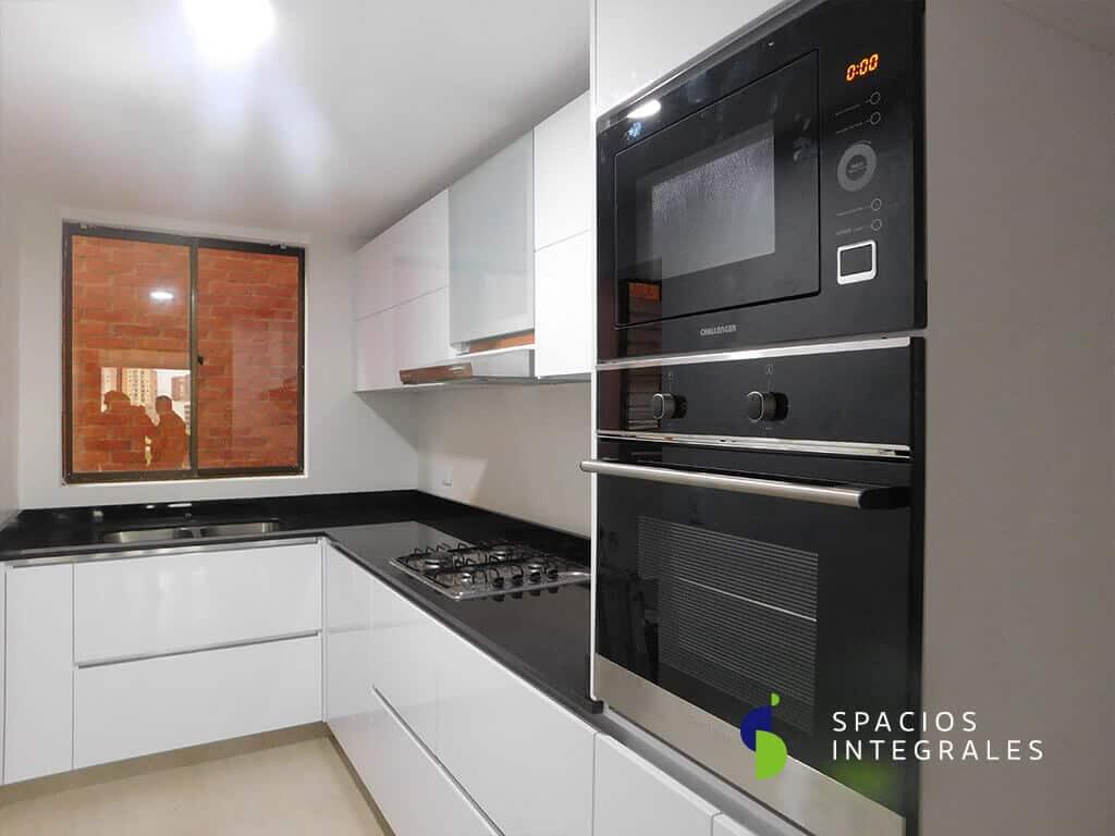 Cocina Integral en L elaborada en Poliretano, puerta marco aluminio y vidrio sanblasting.