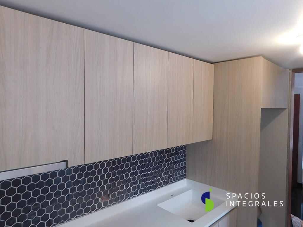 Cocina Integral elaborada con Mesón en Hi-Macs Alpine White, poceta en la misma pieza.