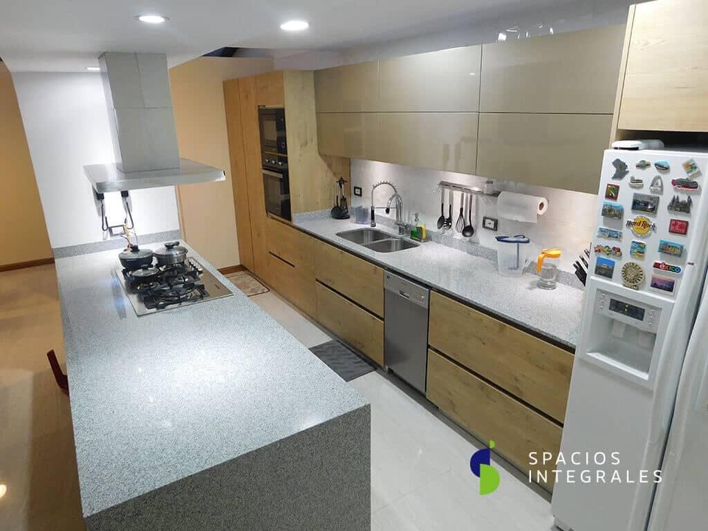 Cocina Integral con mesón en granito natural Jaspe en una sola placa, electrodomésticos Challenger.