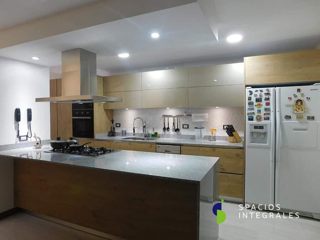 Cocina Integral modular en combinación de materiales aglomerados, puertas superiores con mecanismo Freefold.