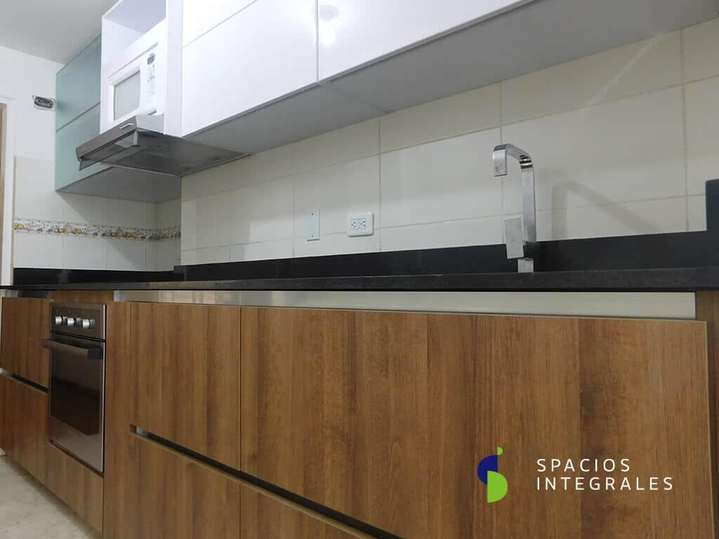 Cocina Integral elaborada en Melamina Tablemac, en combinación con Poliuretano. Mesón Granito Negro Absoluto.