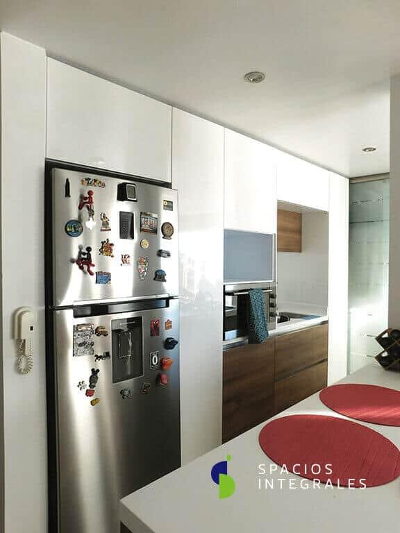 Cocina integral melamina color blanco y madera con mueble sobre nevera e isla con torre